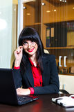 Smiling woman with glasses sits at a table in the office Royalty Free Stock Photo