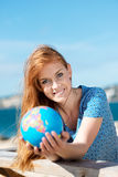 Smiling woman with a globe at the seaside Royalty Free Stock Photos