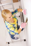 Smiling woman in gloves doing renovations at home. Repair, renovation and home concept - smiling woman in gloves doing renovations at home royalty free stock photos