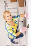 Smiling woman in gloves doing renovations at home. Repair, renovation and home concept - smiling woman in gloves doing renovations at home royalty free stock photo