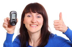 Smiling woman with glucose meter showing thumbs up Stock Images