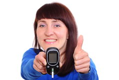 Smiling woman with glucose meter showing thumbs up Stock Photo