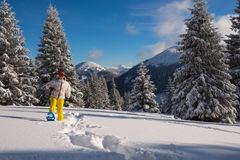 Smiling woman goes on snowshoes in the winter mountains Royalty Free Stock Photography