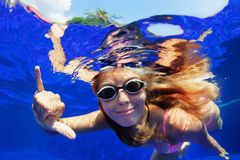 Smiling woman in goggles swim underwater, showing hand sign Shaka royalty free stock photos
