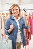 Smiling woman going shopping and showing credit card Stock Photos