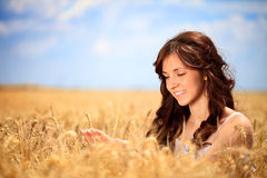 Smiling woman in golden wheat Royalty Free Stock Photo
