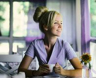 Smiling woman in a good mood with cup of coffee. Sitting in cafe. Bright sunny morning royalty free stock photo