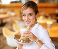 Smiling woman in a good mood with cup of coffee sitting in cafe. Royalty Free Stock Photo