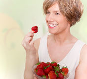 Smiling woman in good mood eating strawberries. Stock Photos