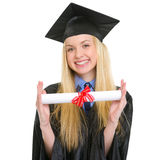 Smiling woman in graduation gown showing diploma Royalty Free Stock Image