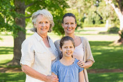 Smiling woman with grandmother and granddaughter at park. Portrait of a smiling women with grandmother and granddaughter at the park Royalty Free Stock Photography