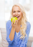 Smiling woman with green apple at home Royalty Free Stock Photos