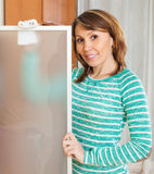 Smiling  woman in green cleaning  glass Stock Image