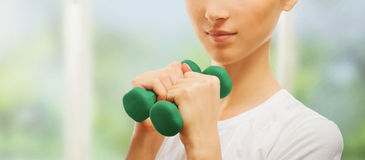 Smiling woman with green dumbbell Stock Images