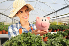 Smiling woman in greenhouse, with piggy bank, Stock Photography