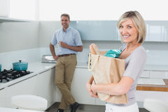 Smiling woman with grocery bag and man in background at kitchen Stock Image