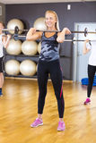 Smiling woman in group doing squat exercises at fitness gym Royalty Free Stock Photo