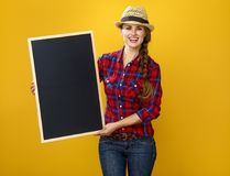 Smiling woman grower isolated on yellow showing blank board. Healthy food to your table. Portrait of smiling young woman grower in checkered shirt isolated on Royalty Free Stock Photography