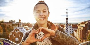 Smiling woman at Guell Park showing heart shaped hands. Barcelona signature style. smiling modern woman in coat at Guell Park in Barcelona, Spain showing heart Royalty Free Stock Photo