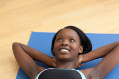 Smiling woman in gym clothes doing sit-ups. At home Stock Photo