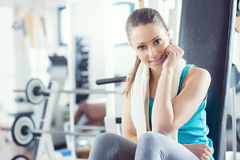 Smiling woman at gym relaxing on exercise bench Stock Photos