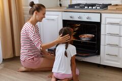 Smiling woman with hair ban touching her little daughter head while kid sitting backwards to camera and looking at oven with