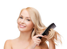 Smiling woman with hair brush Royalty Free Stock Photo
