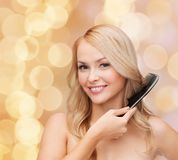 Smiling woman with hair brush Stock Images