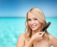 Smiling woman with hair brush Royalty Free Stock Image