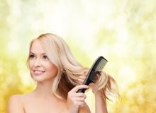 Smiling woman with hair brush Royalty Free Stock Images