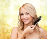 Smiling woman with hair brush Royalty Free Stock Photography
