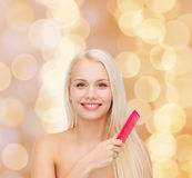 Smiling woman with hair brush Stock Photo