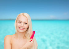 Smiling woman with hair brush Stock Photos