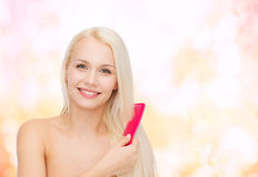 Smiling woman with hair brush Stock Image
