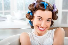 Smiling woman with hair curlers Stock Image
