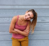 Smiling woman with hair in ponytail and arms crossed. Portrait of smiling woman with hair in ponytail and arms crossed Stock Image