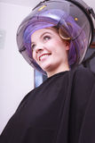 Smiling woman hair rollers curlers hairdryer hairdressing beauty salon. Smiling young woman female client in hairdressing beauty salon. Girl in hair rollers Stock Image
