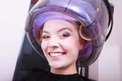 Smiling woman hair rollers curlers hairdryer hairdressing beauty salon. Smiling young woman female client in hairdressing beauty salon. Girl in hair rollers Royalty Free Stock Image