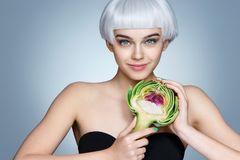 Smiling woman with half of artichoke. Stock Photography
