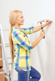 Smiling woman hammering nail in wall Stock Photos