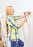 Smiling woman hammering nail in wall Stock Photos