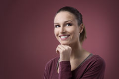 Smiling woman with hand on chin stock image