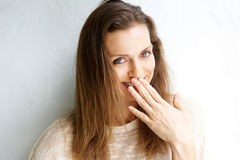 Smiling woman with hand covering mouth Royalty Free Stock Photography