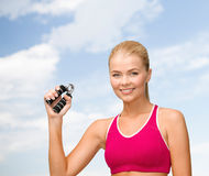 Smiling woman with hand expander. Fitness, healthcare and dieting concept - beautiful sporty woman with hand expander Royalty Free Stock Image