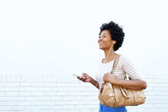 Smiling woman with handbag listening to music Royalty Free Stock Images