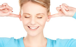 Smiling woman with hands over ears Stock Image