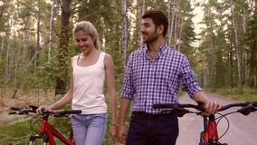 Smiling woman and handsome man walking together holding their bicycles. And talking to each other after a good ride. They like each other and enjoy their time stock video footage
