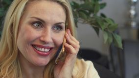 A smiling woman has a phone conversation stock video