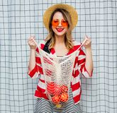 Smiling woman in hat and striped jacket with net bag. Portrait of a young smiling woman in hat and striped jacket with net bag on checkered background stock photography