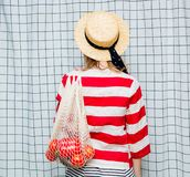 Smiling woman in hat and striped jacket with net bag. Portrait of a young smiling woman in hat and striped jacket with net bag on checkered background stock photo